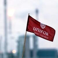 Un drapeau d'Unifor en avant-plan avec les installations de la raffinerie Co-op de Regina en arrière-plan.