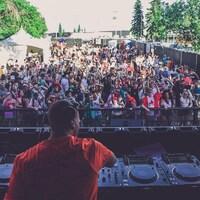 Un DJ joue devant une foule en extérieur.