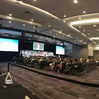 Les élus locaux sont installés sur des chaises dans une grande salle de conférence et écoutent des discours retransmis sur de grands écrans.
