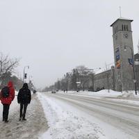 Deux étudiants marchent sur le trottoir enneigé du campus.