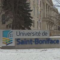 Une grande enseigne indique « Université de Saint-Boniface ». Sur le sol, on voit de la neige.