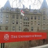 Une femme marche devant le bâtiment principal de l'Université de Winnipeg, rue Portage.