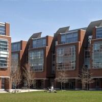 Un bâtiment avec des étudiants sur la pelouse.