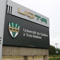 Pancarte à l'entrée du campus de l'UQTR devant des arbres feuillus.