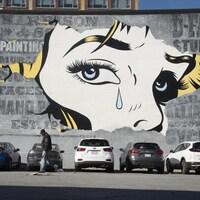 Une murale du visage d'une femme qui verse une larme peinte sur un bâtiment de Montréal.