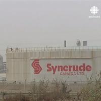 Un silo avec le nom de Syncrude en premier plan, avec les tours de l'usine à l'arrière.