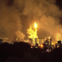 Des flammes et de la fumée s'élèvent d'une usine.