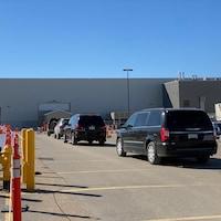 Des voitures sont en file en attente de pouvoir entrer dans la clinique au volant à Regina pour que les occupants puissent se faire vacciner.