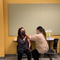 Une femme reçoit un vaccin contre la COVID-19.
