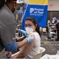 Une femme reçoit sa première dose de vaccin.
