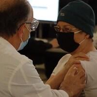 Une femme se fait vacciner contre la COVID-19 dans une église à Rimouski.