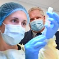 Le premier ministre de l'Ontario, Doug Ford, regarde une infirmière préparer une dose de vaccin contre la COVID-19.