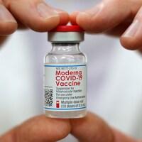 Deux mains tiennent une fiole du vaccin de Moderna contre la COVID-19, à West Haven, Connecticut, États-Unis, le 17 février 2021.