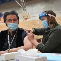 Un homme qui porte un masque se fait inoculer une dose de vaccin par une femme qui porte un masque et une visière de protection.