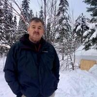Un homme pose devant une forêt en hiver.