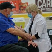 Un homme reçoit une dose de vaccin contre la COVID-19, le 11 mars 2021 à Matane.