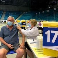 Une infirmière administre une dose de vaccin contre la COVID-19 dans un aréna transformé en séance de vaccination.