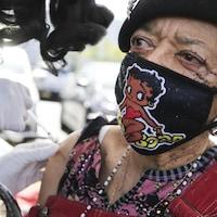 La dame, qui porte un masque de Betty Boop, reçoit son vaccin sur l'épaule.