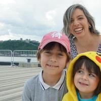Une mère derrière ses deux enfants, dont une petite fille porte un costume de Pikachu