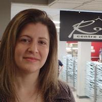 Valérie Laforest, directrice de la culture, des sports, des loisirs et du développement social à l'arrondissement Rivière-des-Prairies–Pointe-aux-Trembles, pose devant une affiche sur laquelle est écrit Roussin centre communautaire.