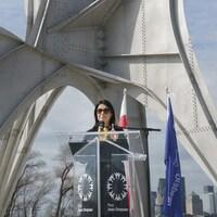 Valérie Plante, dehors, devant une structure et derrière un lutrin pour une conférence de presse.