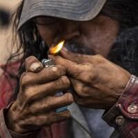 Un homme fume de la drogue dans le quartier Downtown Eastside à Vancouver.