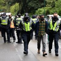 Des policiers de Vancouver procèdent à l'arrestation d'un militant d'Extinction Rebellion.