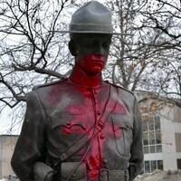Une statue d'un agent de la GRC en bronze recouverte d'un graffiti rouge.