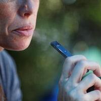 Une femme fume une cigarette électronique.