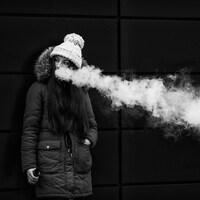 Une jeune femme adossée à un mur vapote. Elle porte une tuque et un manteau d'hiver.