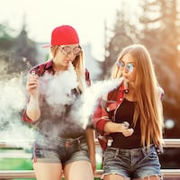 Deux adolescentes vapotent.