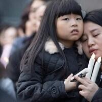 Une femme porte une petite fille et elle tiennent toutes les deux des bougies électriques.