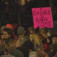 Une foule de personnes au parc Victoria de Regina et une personne tient une pancarte rose.