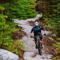 Un cycliste descend un sentier rocheux