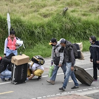 Un groupe d'hommes et de femmes au milieu d'une route portant des bagages.