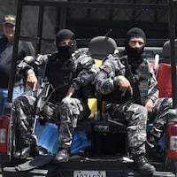 Deux hommes en uniforme, le visage masqué et portant des fusils automatiques, sont assis dans la boîte arrière d'une camionnette.