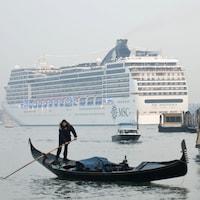Un navire de croisière dans le Grand canal de Venise, devant un batelier sur sa petite embarcation.