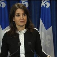Véronique Hivon devant des drapeaux du Québec.