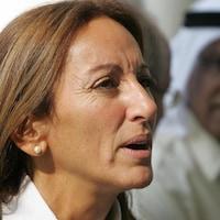 Une femme aux cheveux brun-roux, qui a la bouche ouverte et regarde droit devant elle, semble répondre à quelqu'un.