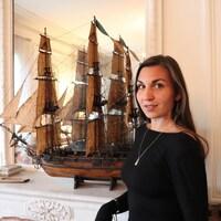 Joëlle Preston pose dans un espace intérieur, devant un foyer sur lequel trône une réplique de voilier.