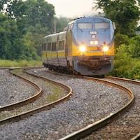 Un train de passagers circule sur une voie ferrée sinueuse en été.