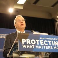 Le ministre derrière un podium