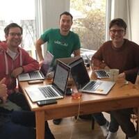 Les membres de l'équipe de VidDay assis autour d'une table travaillent chacun à leur ordinateur.