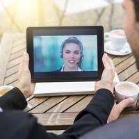 Deux personnes vues de dos discutant avec une femme via une vidéoconférence.