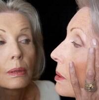 Une femme se regarde le visage dans un miroir.