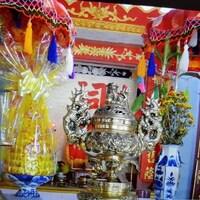 Un autel des ancêtres multicolores dans lequel sont placés un pot de fleur et objets décoratifs dont des bougies
