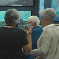 Des visiteurs masqués se pressent devant des peintures d'artistes.