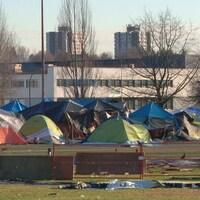 Des tentes dans un parc, avec des édifices en arrière-plan.
