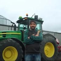 Vincent Pawluski pose devant un tracteur avec sa télécommande.
