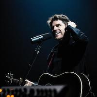 Un homme tient une guitare sur scène.
